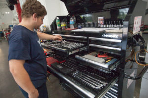 man selecting wrench from tool cabinet