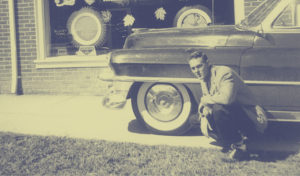 Young Man Kneeling Next to a 1950s Car