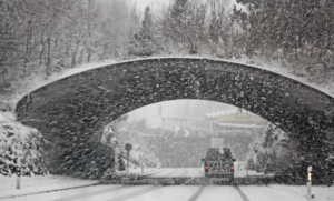 Car driving under a bridge in the snow