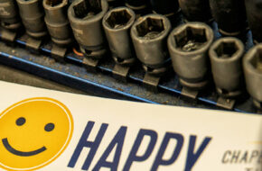 "photo of a set of wrenches beside a bumper sticker with a yellow smiley face that reads ""Drive Happy"" and a blue ball cap with a yellow smiley face"