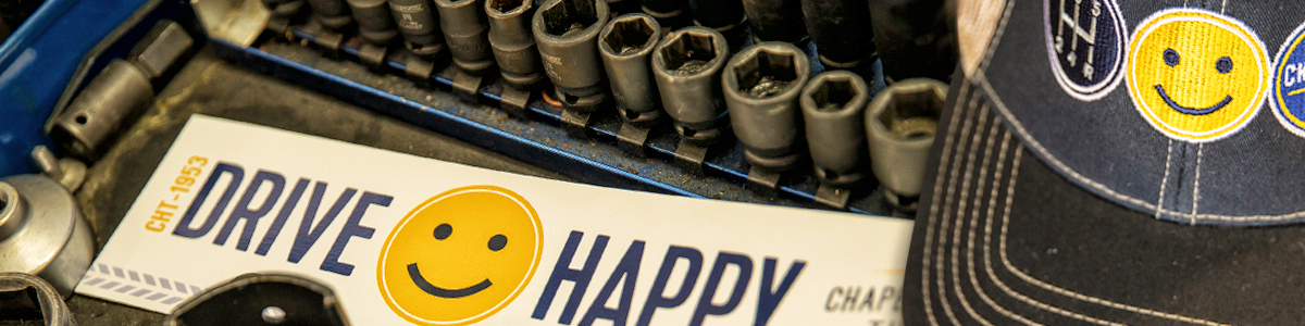 """photo of a set of wrenches beside a bumper sticker with a yellow smiley face that reads """"Drive Happy"""" and a blue ball cap with a yellow smiley face"""