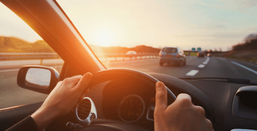 Person holding a steering wheel at sunset