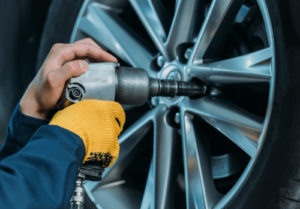 Mechanic changing a tire with a wheel lock key