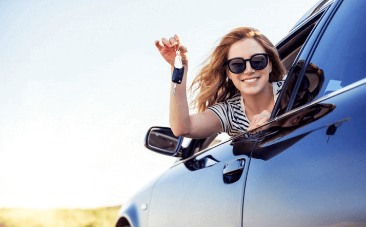 woman holding car keys out the window